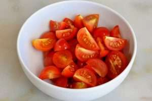 corte o tomate cereja em 4 pedaços