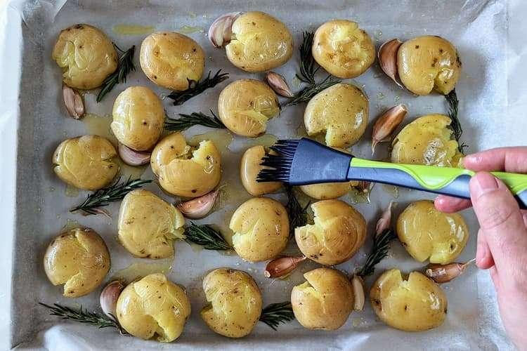 regue e pincele azeite sobre as batatas